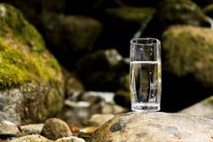 Διαφανής ένας γυαλί/γυαλί με το ορυκτό νερό ποταμού βουνών στέκεται σε μια πέτρα εκτός από τον κολπίσκο ποταμών βουνών Στοκ Εικόνες