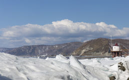 Διαφανής μπλε πάγος hummocks Baikal λιμνών στην ακτή Άποψη χειμερινών τοπίων της Σιβηρίας με το φάρο Χιονισμένος πάγος Στοκ Εικόνα