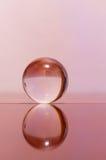 Διαφανής σφαίρα γυαλιού στην ανοικτό ροζ επιφάνεια υποβάθρου και καθρεφτών Στοκ Εικόνες
