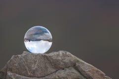 Διαφανής σφαίρα γυαλιού στην κορυφή του βράχου και του σκοταδιού Στοκ Φωτογραφία