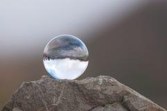 Διαφανής σφαίρα γυαλιού στην κορυφή του βράχου και του σκοταδιού Στοκ Εικόνες