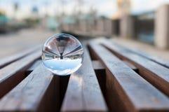 Διαφανής σφαίρα γυαλιού στο ξύλινο slats υπόβαθρο Στοκ Εικόνες