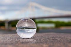 Διαφανής σφαίρα γυαλιού στο υπόβαθρο γεφυρών και Στοκ Εικόνες