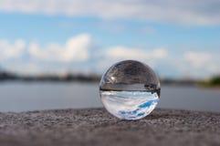 Διαφανής σφαίρα γυαλιού στο υπόβαθρο ποταμών και Στοκ Εικόνα