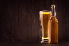 Διαφανή μπουκάλι μπύρας και γυαλί weizen με το χρυσό ξανθό γερμανικό ζύθο στο σκοτεινό καφετή ξύλινο πίνακα, διάστημα αντιγράφων, Στοκ φωτογραφία με δικαίωμα ελεύθερης χρήσης