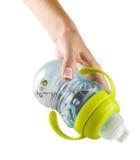 Διαφανή φλυτζάνι γουλιών και χέρι μητέρων - θηλή - ειρηνιστής botle για το νερό ή το γάλα που απομονώνεται στο λευκό με την πορεί Στοκ Φωτογραφίες