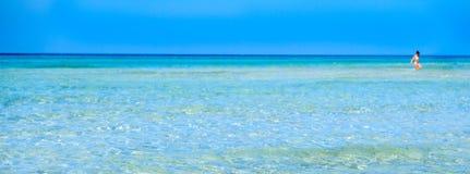 Διαφανή saltwater περιπάτων κοριτσιών θάλασσας υποβάθρου θαμπάδων νερού οριζόντια κρυστάλλινα επίπεδα Στοκ Φωτογραφίες
