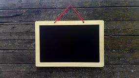 διαφημιστικό κενό χαρτόνι Κενός μαύρος πίνακας ενάντια στον ξύλινο τοίχο υποβάθρου απόθεμα βίντεο