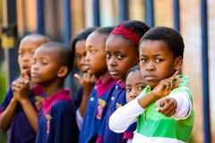 Διαφορετικά αφρικανικά παιδιά δημοτικού σχολείου που κάνουν το φυσικό μάθημα PT άσκησης στοκ εικόνες