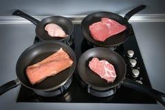 Διαφορετικά είδη κρέατος στα τηγάνια Στοκ Εικόνες