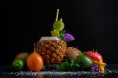 Διαφορετικά εξωτικά φρούτα Φλυτζάνι ανανά, ολόκληρο αβοκάντο, κόκκινοι γρανάτης και μέντα σε ένα μαύρο υπόβαθρο συστατικά φυσικά Στοκ Φωτογραφία