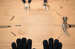 Διαφορετικά εργαλεία κατασκευής που συσσωρεύονται σε έναν κύκλο στο ξύλινο υπόβαθρο χρυσά πλήκτρα σπιτιών δάχτυλων κατασκευής ένν Στοκ Φωτογραφία