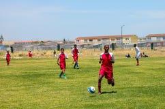 Διαφορετικά παιδιά που παίζουν το ποδόσφαιρο ποδοσφαίρου στο σχολείο Στοκ Εικόνες