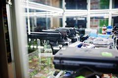 Διαφορετικά πυροβόλα όπλα και περίστροφα στα όπλα καταστημάτων ραφιών στο CE καταστημάτων Στοκ Εικόνες