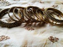 Διαφορετικά σχεδιασμένα χρυσά βραχιόλια στο υπόβαθρο μεταξιού στοκ φωτογραφία