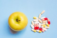 Διαφορετικά φαρμακευτικά χάπια και η φρέσκια πράσινη Apple στο μπλε υπόβαθρο Στοκ Εικόνες