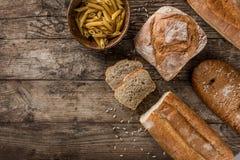 Διαφορετικά φρέσκα ζυμαρικά προϊόντων ψωμιού και αλευριού στο αγροτικό ξύλινο υπόβαθρο στοκ φωτογραφίες