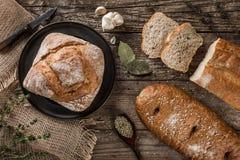 Διαφορετικά φρέσκα ψωμί και καρύκευμα στο αγροτικό ξύλινο υπόβαθρο Δημιουργικό σχεδιάγραμμα φιαγμένο από ψωμί στοκ φωτογραφίες
