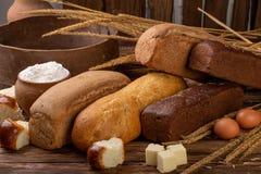 Διαφορετικά φρέσκα ψωμί και spikelets του σίτου στο αγροτικό ξύλινο υπόβαθρο Δημιουργικό σχεδιάγραμμα φιαγμένο από ψωμί τρόφιμα έ στοκ εικόνα
