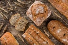 Διαφορετικά φρέσκα ψωμί και spikelets του σίτου στο αγροτικό ξύλινο υπόβαθρο Δημιουργικό σχεδιάγραμμα φιαγμένο από ψωμί στοκ φωτογραφίες
