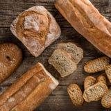 Διαφορετικά φρέσκα ψωμί και spikelets του σίτου στο αγροτικό ξύλινο υπόβαθρο στοκ εικόνες