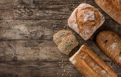 Διαφορετικά φρέσκα ψωμί και spikelets του σίτου στο αγροτικό ξύλινο υπόβαθρο Δημιουργικό σχεδιάγραμμα φιαγμένο από ψωμί στοκ εικόνες