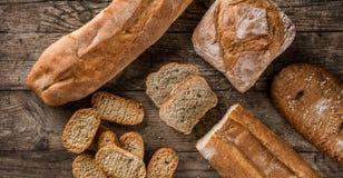 Διαφορετικά φρέσκα ψωμί και spikelets του σίτου στο αγροτικό ξύλινο υπόβαθρο Δημιουργικό σχεδιάγραμμα φιαγμένο από ψωμί στοκ εικόνα με δικαίωμα ελεύθερης χρήσης
