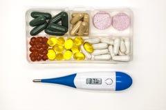 Διαφορετικά χάπια, φάρμακα, τα χάπια στο κιβώτιο για την κινηματογράφηση σε πρώτο πλάνο φαρμάκων με το θερμόμετρο στο άσπρο υπόβα Στοκ Εικόνες