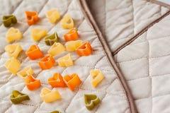Διαφορετικά χρωματισμένα ιταλικά ζυμαρικά στη μορφή καρδιών στα κλωστοϋφαντουργικά προϊόντα κουζινών τρόφιμα μπουλεττών ανασκόπησ Στοκ Εικόνα