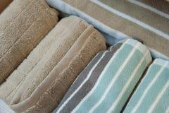Διαφορετικά χρώματα της πετσέτας μπροστά από το υπόβαθρο τυπωμένων υλών βαμβακιού Στοκ Εικόνα