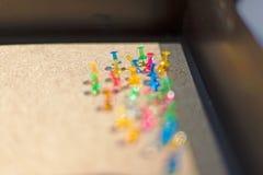 Διαφορετικά χρώματα Pushpin που καρφώνονται σε έναν πίνακα φελλού Στοκ Φωτογραφίες