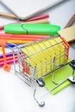 Διαφορετικές ζωηρόχρωμες σχολικές προμήθειες που ανατρέπονται από λίγο κάρρο αγορών Στοκ Εικόνες