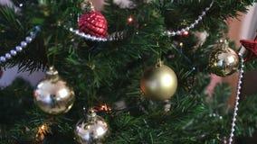 Διαφορετικές σφαίρες και χρυσά παιχνίδια στους κλάδους του χριστουγεννιάτικου δέντρου Γιρλάντα Χριστουγέννων με τα φω'τα στο χρισ απόθεμα βίντεο