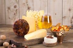 Διαφορετική κλασική επιλογή τυριών, σε έναν παλαιό ξύλινο πίνακα, καρύδια, πρόχειρα φαγητά και ένα ποτήρι της μπύρας και ενός μπο στοκ εικόνες με δικαίωμα ελεύθερης χρήσης