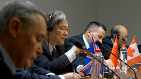 Διαφορετική ομάδα επιχειρηματιών στα κοστούμια που συζητούν στη Διεθνή Διάσκεψη ή που συναντιούνται στη σύγχρονη αίθουσα συνεδρίω απόθεμα βίντεο