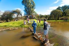 Διαφορετικοί άνθρωποι που διασχίζουν μια λίμνη στο υπαίθριο φεστιβάλ στοκ φωτογραφίες
