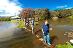 Διαφορετικοί άνθρωποι που διασχίζουν μια λίμνη στο υπαίθριο φεστιβάλ στοκ εικόνα με δικαίωμα ελεύθερης χρήσης