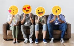 Διαφορετικοί άνθρωποι που κάθονται και που καλύπτουν το πρόσωπο με τους πίνακες emojis στοκ εικόνα