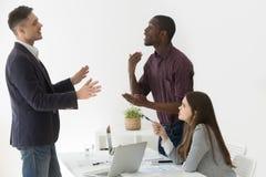 Διαφορετικοί αφρικανικοί και καυκάσιοι συνάδελφοι που έχουν τη διαφωνία στην ομάδα στοκ εικόνα