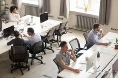 Διαφορετικοί εργαζόμενοι γραφείων που χρησιμοποιούν τους υπολογιστές στο σύγχρονο εταιρικό διάστημα στοκ φωτογραφία με δικαίωμα ελεύθερης χρήσης