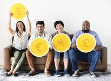 Διαφορετικοί εργαζόμενοι που κάθονται και που κρατούν τα εικονίδια νομίσματος Στοκ Φωτογραφίες
