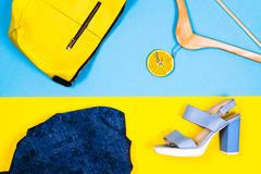Διαφορετικοί ιματισμός και εξαρτήματα γυναικών ` s στο φωτεινό κίτρινο και μπλε υπόβαθρο Επίπεδος βάλτε τη μόδα, έννοιες Στοκ Εικόνες