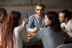 Διαφορετικοί νέοι που μιλούν και που έχουν τη διασκέδαση μαζί στον καφέ Στοκ Εικόνες