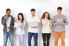 Διαφορετικοί σπουδαστές που χρησιμοποιούν τις συσκευές, που στέκονται στη γραμμή Στοκ Εικόνες