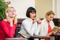 Διαφορετικοί τρόποι να χαλαρώσει κορίτσια στον καφέ κοινωνική ποικιλομορφία μουσική ακούσματος βιβλίο ανάγνωσης πίνοντας καφές Fr στοκ εικόνες