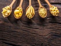 Διαφορετικοί τύποι ζυμαρικών στα ξύλινα κουτάλια στον πίνακα Τοπ όψη στοκ εικόνες με δικαίωμα ελεύθερης χρήσης