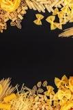 Διαφορετικοί τύποι ζυμαρικών στο μαύρο υπόβαθρο Στοκ Εικόνες