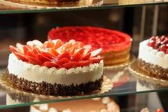 Διαφορετικοί τύποι κέικ στην επίδειξη γυαλιού καταστημάτων ζύμης στοκ εικόνες