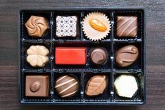Διαφορετικοί τύποι καραμελών σοκολάτας σε ένα ξύλινο υπόβαθρο/εύγευστων καραμελών σοκολάτας στο παράθυρο δώρων στην επιτραπέζια κ στοκ εικόνα με δικαίωμα ελεύθερης χρήσης