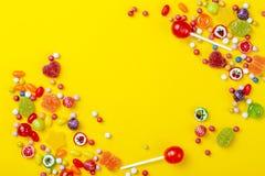 Διαφορετικοί τύποι καραμελών στο κίτρινο υπόβαθρο, διάστημα αντιγράφων στοκ φωτογραφία